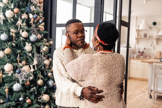 Relacionamento duradouro. mulher simpática e bonita ao lado do marido, comemorando o natal