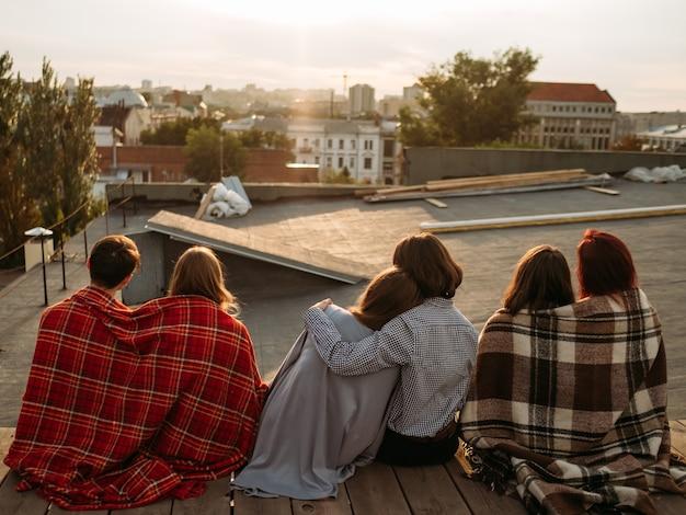 Relacionamento e namoro adolescente. vista traseira de diversos casais apaixonados sentados juntos em um telhado apreciando o pôr do sol