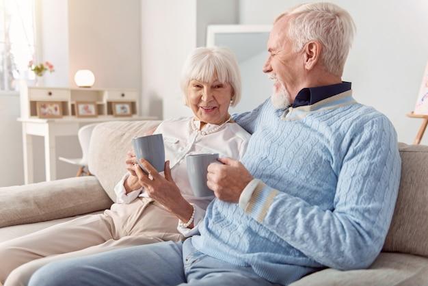 Relacionamento precioso. casal de idosos felizes sentados no sofá e se unindo enquanto bebem café juntos