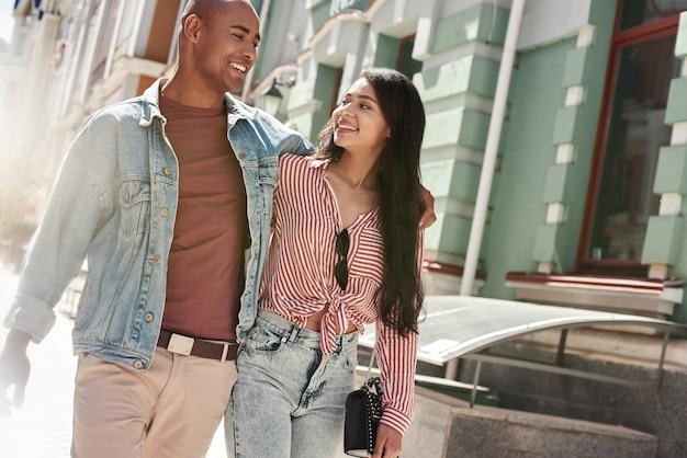 Relacionamento romântico jovem casal diversificado caminhando na rua da cidade se abraçando, olhando um para o outro