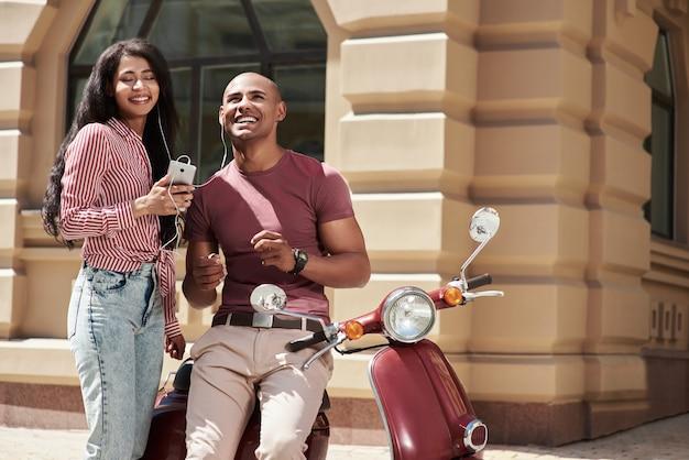 Relacionamento romântico, jovem casal diversificado usando fones de ouvido, sentado em uma bicicleta na rua da cidade