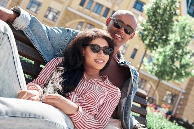 Relacionamento romântico jovem casal diversificado usando óculos escuros, sentado no banco na rua da cidade