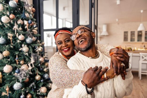 Relacionamentos felizes. mulher africana encantada em pé atrás do marido enquanto sorri
