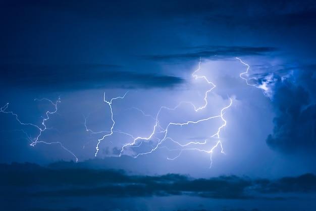 Relâmpago da tempestade do trovão no fundo escuro do céu nebuloso na noite.