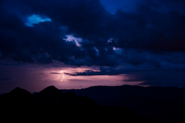Relâmpago e nuvens de tempestade na noite sobre montanhas