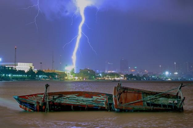 Relâmpagos e um barco virado em pattaya