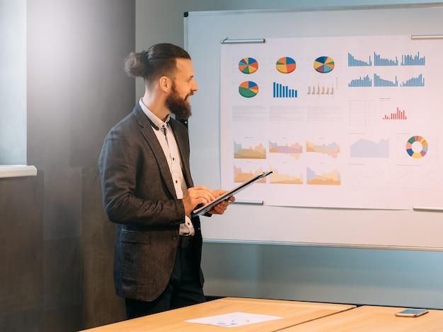 Relatório de análise de negócios. projeto de sucesso. jovem funcionário do sexo masculino fazendo apresentação, usando gráficos no quadro branco.