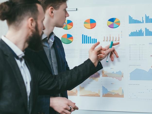 Relatório de análise de negócios. reunião corporativa. colegas revisando gráficos no quadro branco.
