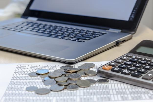 Relatório de contabilidade financeira, moedas, calculadora e taptop na mesa de mesa.