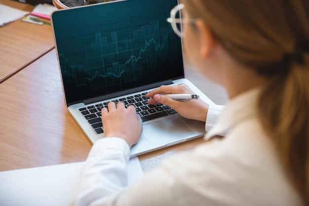 Relatório de digitação. empreendedor caucasiano, mulher de negócios, gerente trabalhando concentrado no escritório. parece serio e ocupado, vestindo um traje clássico. conceito de trabalho, finanças, negócios, sucesso, liderança.