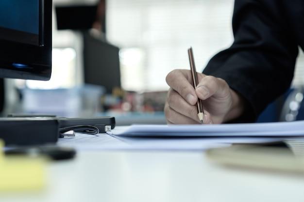 Relatório de documento e conceito de negócio ocupado: as mãos do gerente do empresário segurando um lápis para ler e assinar a papelada ou os arquivos de documentação no fundo do escritório corporativo moderno do computador.