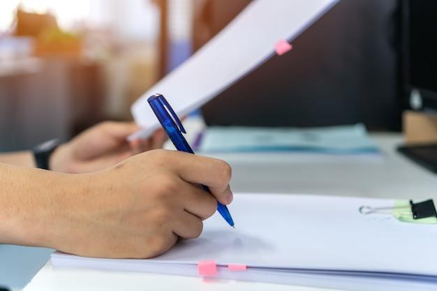Relatório de documento e conceito de negócio ocupado: as mãos do gerente do empresário segurando uma caneta azul para ler e assinar arquivos de papelada ou documentação no fundo do escritório corporativo moderno do computador.