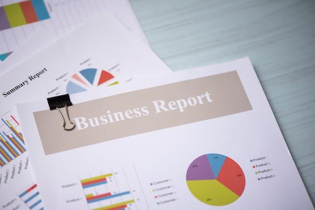 Relatório de documento em papel presente financeiro e relatório de negócios gráfico gráfico na mesa de escritório
