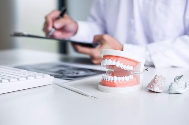 Relatório de escrita médico ou dentista trabalhando com filme de raio-x de dente