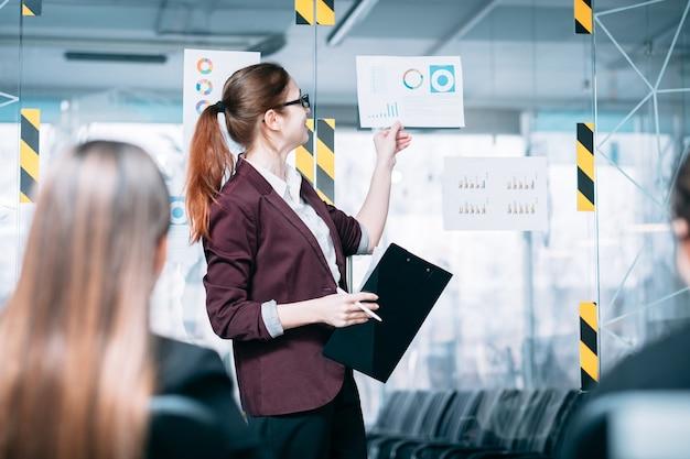 Relatório de estratégia de sucesso. reunião de negócios na sala de reuniões. palestrante corporativo apontando para o documento com diagramas.