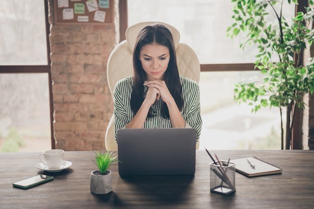 Relatório de leitura de especialista focado em senhora séria sobre netbook no escritório