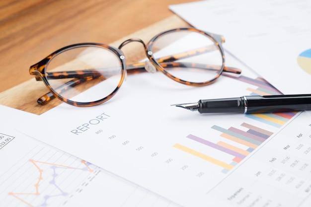 Relatório de negócios da mesa de trabalho de madeira analisa o gráfico, óculos, caneta.