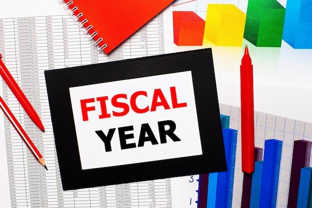 Relatórios e gráficos de cores estão na mesa. também há canetas vermelhas, lápis e papel em uma moldura preta com as palavras ano fiscal. vista de cima
