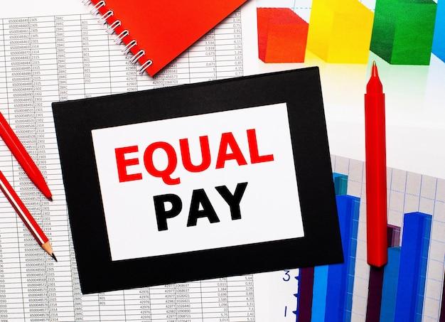 Relatórios e gráficos de cores estão na mesa. também há canetas vermelhas, lápis e papel em uma moldura preta com as palavras igualdade de pagamento. vista de cima