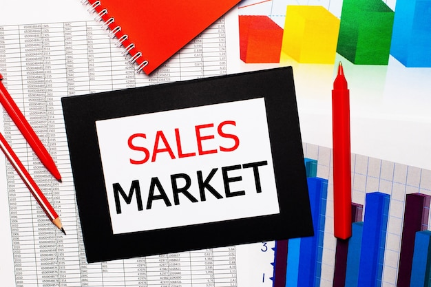 Relatórios e gráficos de cores estão na mesa. também há canetas vermelhas, lápis e papel em uma moldura preta com as palavras mercado de vendas. vista de cima