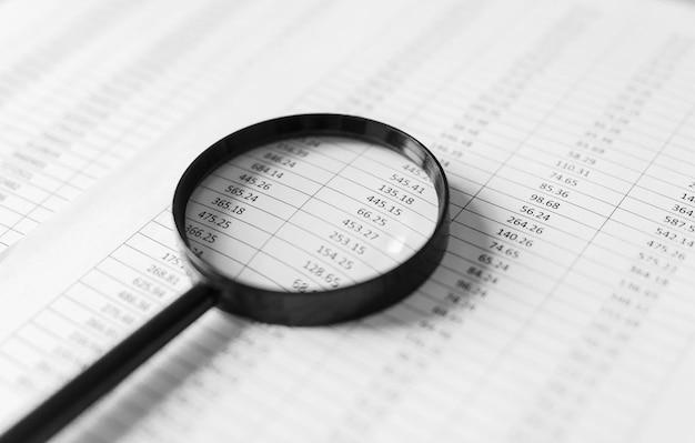 Relatórios financeiros e uma lupa com escritório na mesa.
