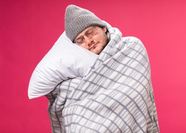Relaxado com os olhos fechados, um homem doente de meia-idade usando um chapéu de inverno e um lenço envolto em um travesseiro xadrez abraçado