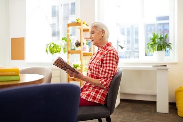 Relaxamento agradável. bela mulher idosa sentada à mesa enquanto lê um livro em casa