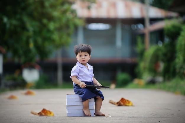 Relaxamento ao ar livre no parque, bebê bonito do bebé tailandês que senta-se no livro.