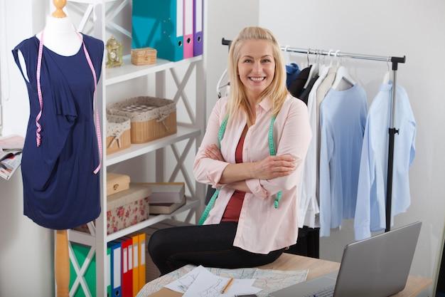 Relaxamento após um trabalho bem sucedido. mulher olhando e em pé perto da mesa na oficina com roupas penduradas. estúdio de design de interiores.