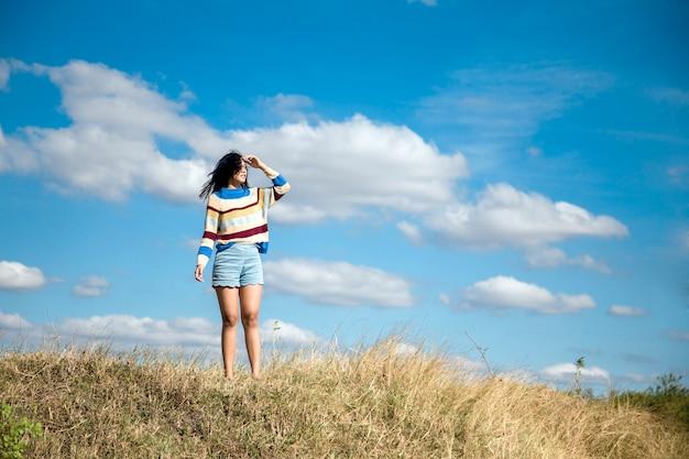 Relaxamento asiático da menina do retrato na colina com céu