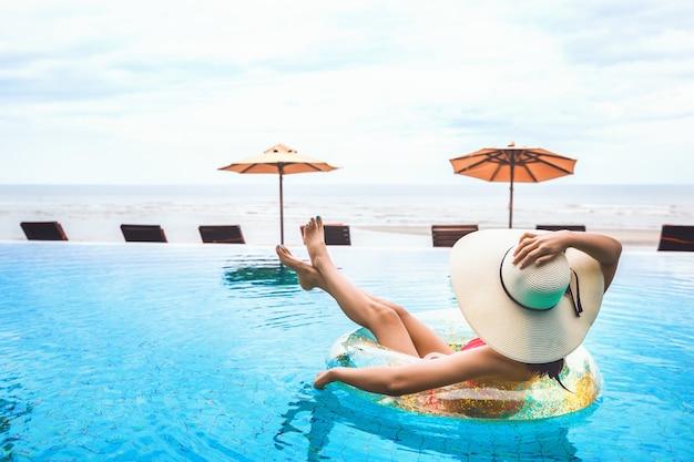 Relaxamento de mulher de biquíni na bóia da piscina
