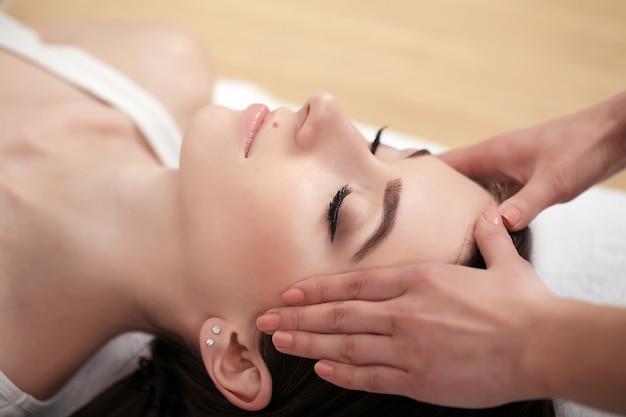 Relaxamento de spa, cuidados com a pele, conceito de prazer saudável, mulher deitada com os olhos fechados, com massagem facial relaxante