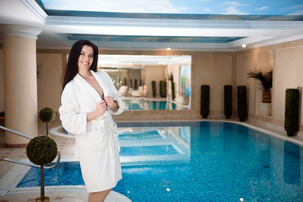 Relaxamento de spa para garota de biquíni perto da piscina no salão spa dia resort