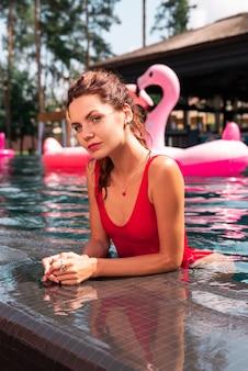 Relaxamento de verão. mulher bonita e alegre sorrindo para você enquanto está na piscina