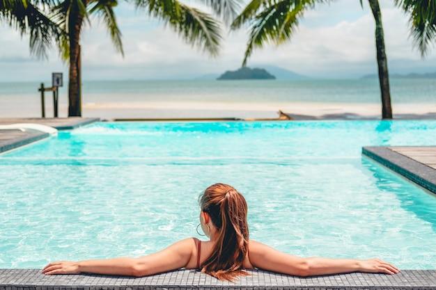 Relaxamento despreocupado da mulher no conceito das férias de verão da piscina