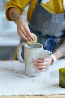 Relaxamento do trabalho com argila crua jovem artista formando jarro de material cerâmico com água