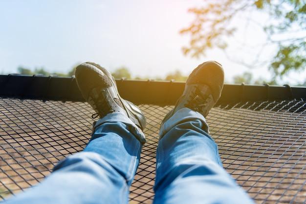Relaxamento dos pés vestindo casual shoesstretching suas pernas na rede. sentir-se gret.