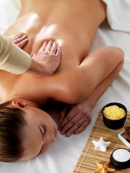 Relaxamento e alegria em massagem para jovem mulher bonita em salão de beleza spa - vertical