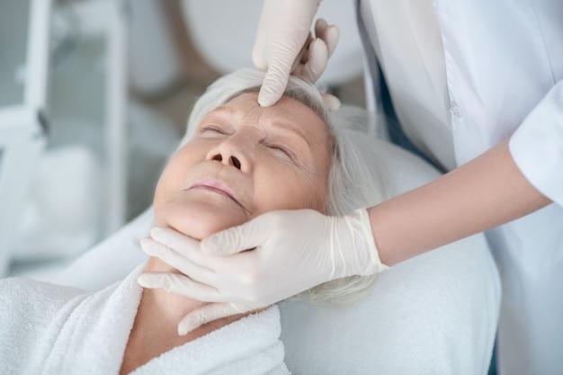 Relaxamento. mulher madura de cabelos grisalhos deitada com os olhos fechados e fazendo uma massagem facial