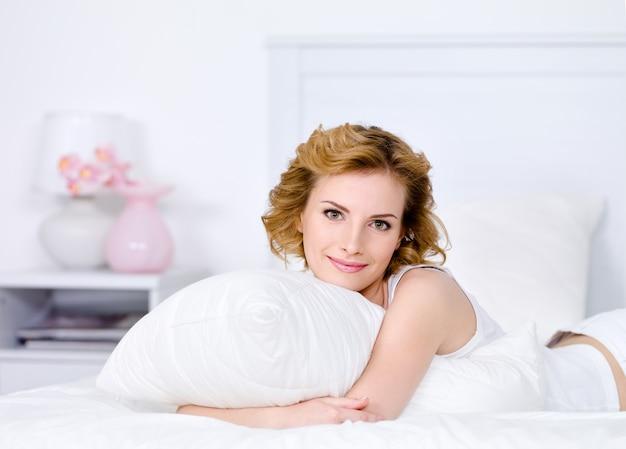 Relaxamento na cama de uma jovem mulher loira e bonita
