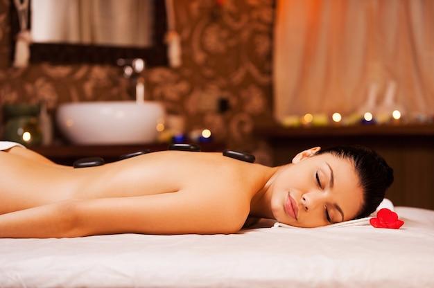 Relaxamento total. vista lateral de uma bela jovem sem camisa deitada na mesa de massagem e mantendo os olhos fechados com pedras de spa nas costas