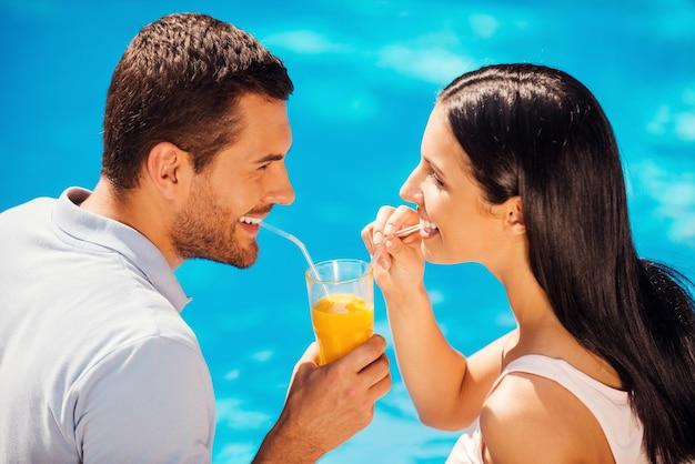 Relaxando à beira da piscina juntos. vista superior de um lindo casal jovem em trajes casuais bebendo coquetel em um copo e sorrindo enquanto sentam-se à beira da piscina