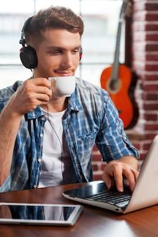 Relaxando com sua música favorita. jovem bonito usando fones de ouvido, trabalhando no laptop e bebendo café enquanto o violão está deitado ao fundo
