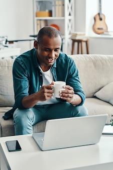 Relaxando em casa. africano jovem e bonito usando um laptop e sorrindo enquanto está sentado dentro de casa