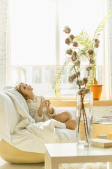 Relaxando em casa. mulher jovem e bonita deitada no sofá com luz solar quente.
