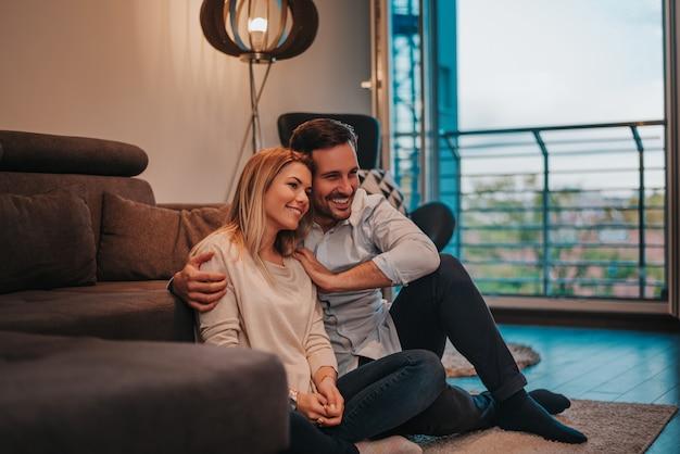 Relaxando em casa nova. casal jovem alegre sentada no chão e abraços.