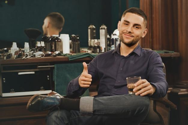 Relaxando em sua barbearia favorita. retrato horizontal de um jovem bonitão relaxante tomando um copo de uísque aparecendo polegares depois de cortar o cabelo na barbearia