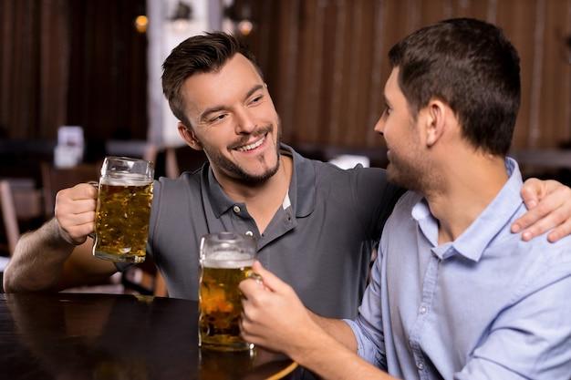 Relaxando em um bar de cerveja. dois jovens alegres bebendo cerveja em bar