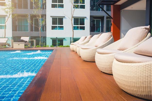 Relaxante cadeiras de vime com travesseiros ao lado da piscina