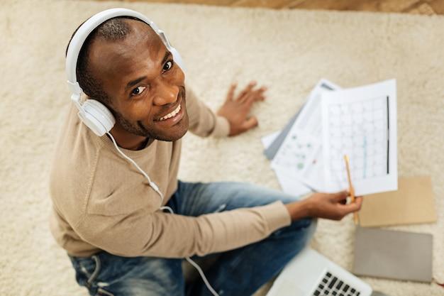 Relaxante. homem afro-americano bonito e inspirado ouvindo música enquanto trabalha e está sentado no chão com seu laptop e olhando alguns papéis